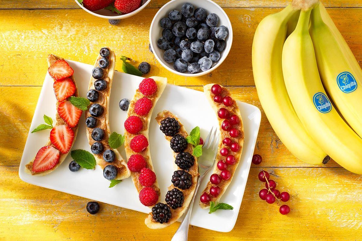 Colazione sana a base di banana split Chiquita con frutti rossi e burro di arachidi