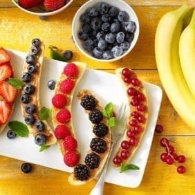 Colazione a base di banana split Chiquita con frutti rossi e burro di arachidi